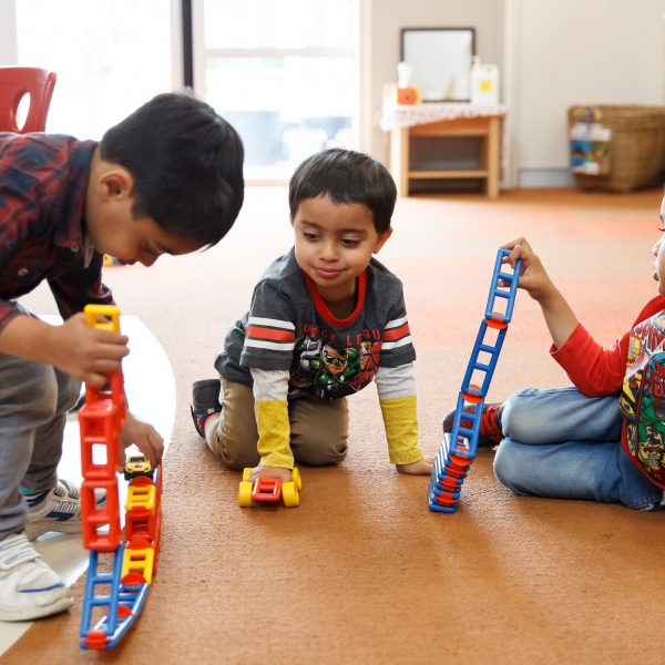 3 young boys playing with connector blocks