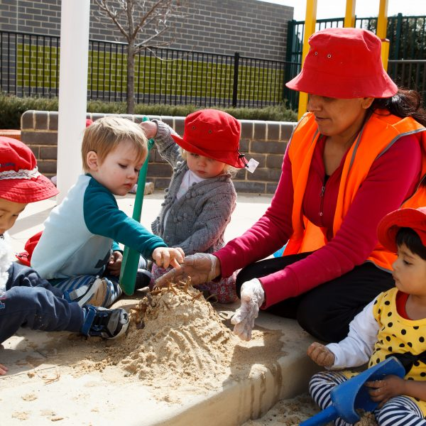 educator playing in sandpit with 4 toddlers