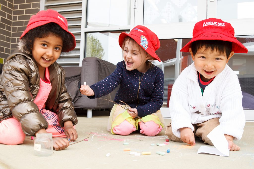 3 preschoolers playing with craft