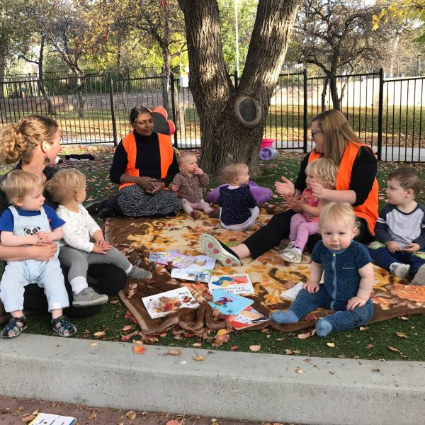 children sitting with educators in park reading books