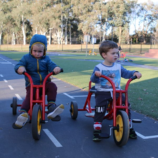two preschoolers riding red tricycles